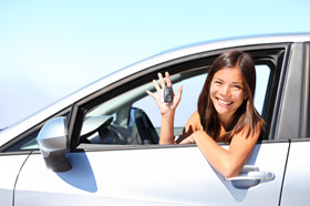 teen girl holding keys to her new car