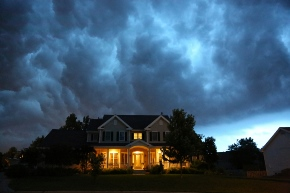 image of house with large storm clouds behind it
