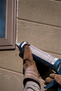image of man caulking an exterior window repair