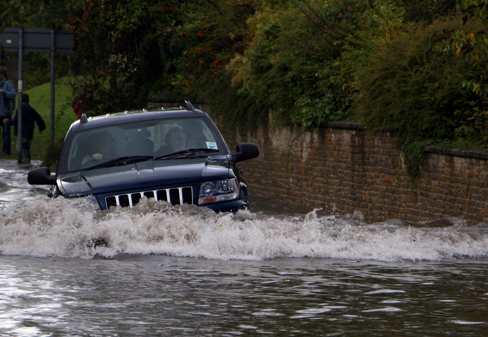 suv driving through deep flood water
