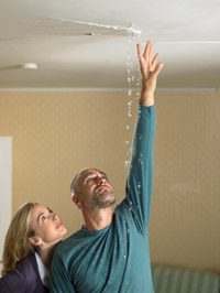 image of couple in home with a leaking ceiling